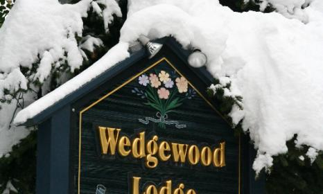 A snowy Wedgewood Lodge sign.